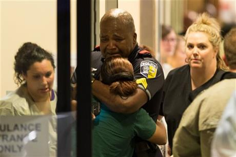 A Dallas Area Rapid Transit police officer receives comfort at the Baylor University Hospital